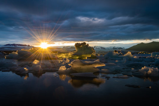 Jokulsarlon Glacier Lagoon. Jökulsárlón is a bay full of ice chunks that breaks off a nearby glacier and floats in to the sea. This dramatic sunset over the ocean of iceburgs is true serendipity.