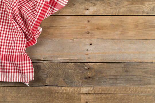 Red checkered dishcloth on brown rustic wooden plank table flat lay top view from above
