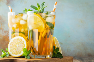 Traditional iced tea with lemon and ice in tall glasses on a wooden rustic table. With copy space