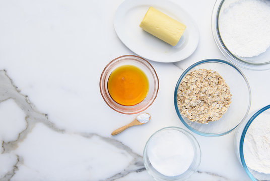 Ingredients for Anzac biscuits a traditional Australian cookie made with butter, desiccated coconut, sugar, golden syrup, rolled oats, baking soda and flour. Flat lay with copy space on marble bench