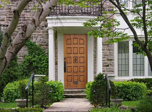 shady front yard of stone house with elegant wooden front door and portico