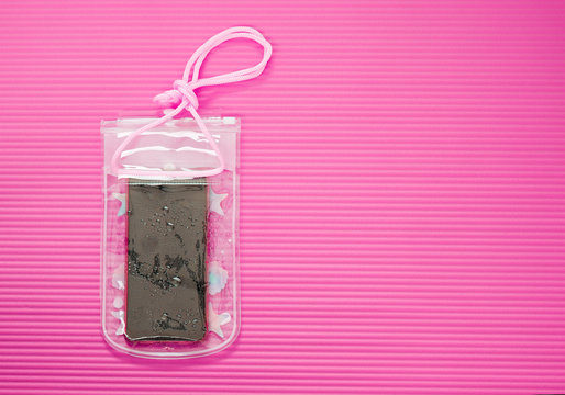 Waterproof Mobile Phone Case with Water Droplets Isolated on Pink Mat Background. Plastic PVC Waterproof Case for Smartphone, Zip Lock Bag Protect. Thai New Year or Water Festival in Thailand.