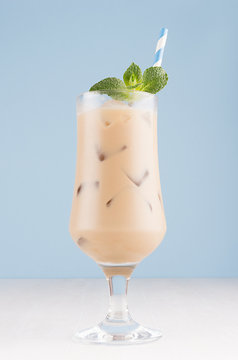 Fresh summer ice coffee in wet exquisite transparent glass with ice cubes, straw, green mint in light blue interior, vertical.