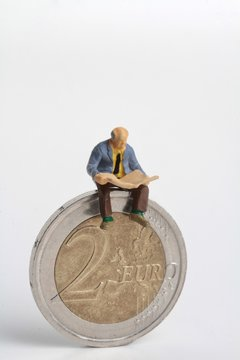 miniature of people reading and euro coins