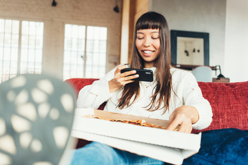 Young beautiful girl eating delivery pizza from the box and taking picture using mobile phone camera