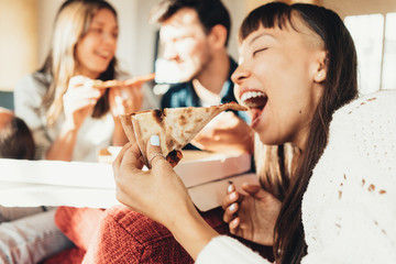Group of friends at home party eating pizza together. Bright sunny apartment