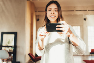 Young woman taking picture in bright loft apartment using mobile phone camera