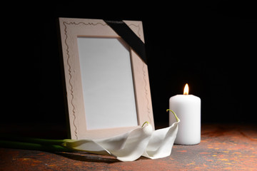 Blank funeral frame, burning candle and flowers on table against dark background