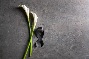 Black funeral ribbon and flowers on grey background Wall mural