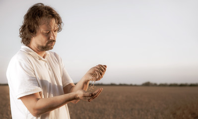 man pours wheat from hand to hand on the background of wheat field