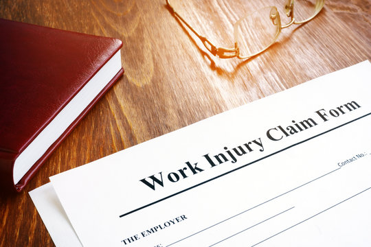 Work injury claim form and glasses on desk.