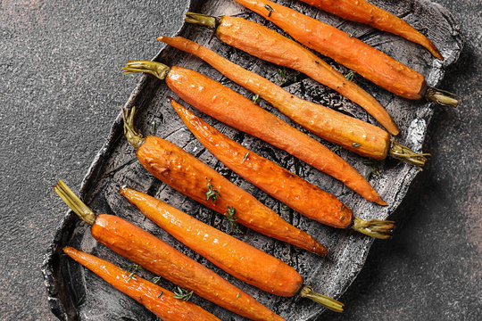 Plate with tasty cooked carrot on grey table