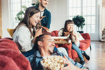 Group of friends at home party fooling and enjoying. Eating pizza, snacks, watching movies and chatting. Bright sunny apartment