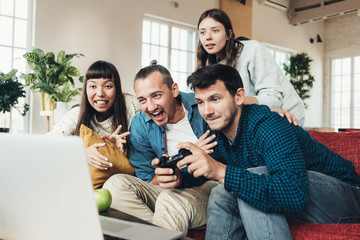 Group of four friends playing video games at home together using controller in big bright apartment