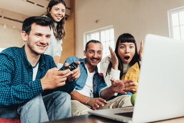 Group of friends playing video games and fooling at home together. Using controller and laptop in big bright apartment