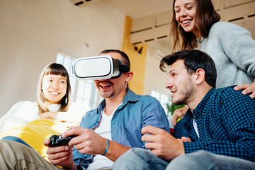 Group of friends playing video computer games and fooling at home together. Using controller and VR headset in big bright apartment