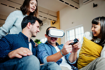 Group of friends playing video computer games and fooling at home together. Using controller and VR glass in big bright apartment
