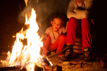Mother and daughter spending quality time by a self-made campfire during adventurous camping trip, playing with fire.