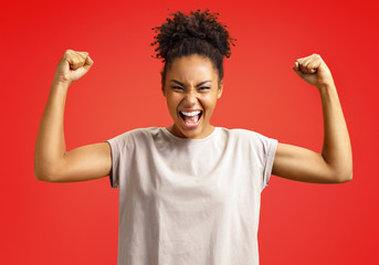 Overjoyed girl clenches fists in triumph. Photo of african american girl wears casual outfit on red background. Emotions and pleasant feelings concept.