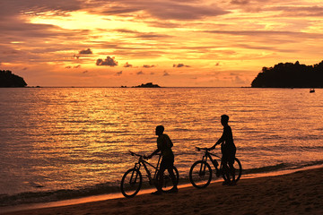Two cyclist relaxing and enjoyed beautiful sunset along the beach in pangkor island, perak malaysia