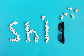 Popcorn and 3d glasses on blue background. Concept pastime, entertainment and cinema. Bad movie concept