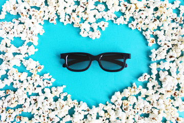 Concept love movie, pastime, entertainment and cinema. Popcorn shape of heart and 3d glasses on blue background.