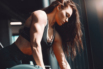 Side view of muscular Caucasian female bodybuilder working out in gym. Become legendary.