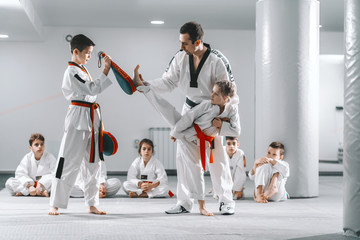 Trainer showing to young girl how to kick kick target. Boy holding target. Tekwondo training concept. Wall mural