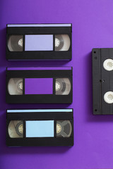 Video cassette on violet background.