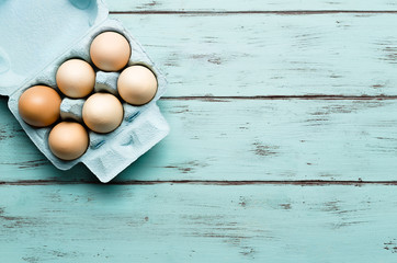 Top view of  eggs on delicate wooden background