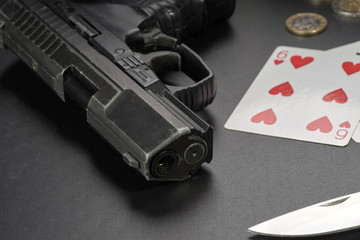 Hanster style: gun card knife and money on a black table