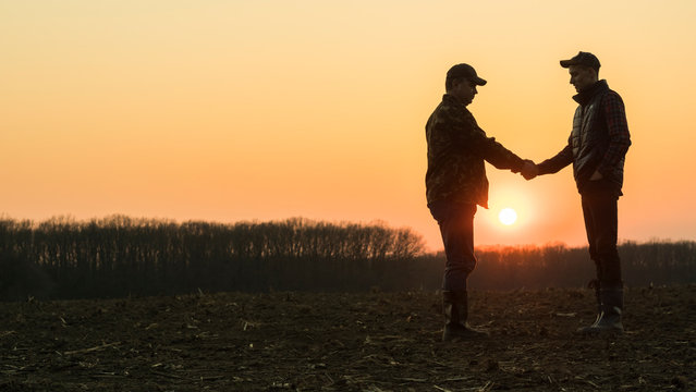 Two male farmers shake hands with each other. Stand on the background of a plowed field at sunset