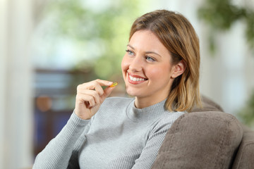 Happy woman takes a vitamin pill on a couch