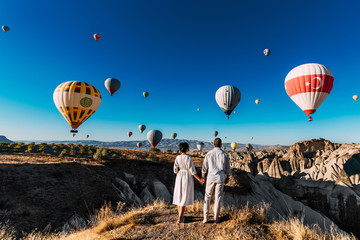 Wedding travel. Honeymoon trip. Couple in love among balloons. A guy proposes to a girl. Couple in love in Cappadocia. Couple in Turkey.  Man and woman traveling. Flying on balloons. Tourists Wall mural