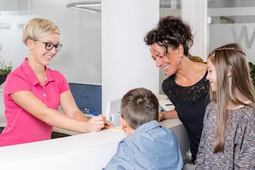 Mutter steht mit ihren Kindern lächelnd im Empfangsbereich einer Zahnarztpraxis mit einer Sprechstundenhilfe