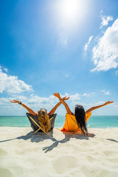 Two Women enjoying their holidays on a transat at the tropical beach