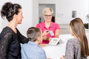 Arzthelferin beim einlesen der Versichertenkarte einer Mutter mit ihren Kindern