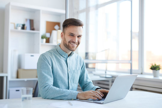 Portrait of handsome young man working in office and smiling happily at camera, copy space