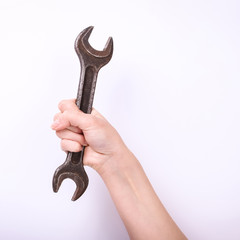 A wrench in the hand of a girl. Symbol of hard work, feminism and labor day. Isolate on white background.
