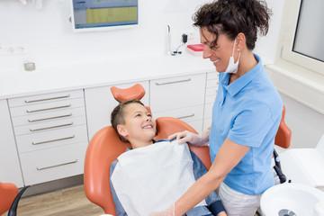 Junge auf dem Zahnarztstuhl, lächelt entspannt zur Assistentin