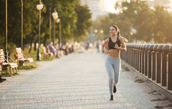 Young sporty woman running on quay in city park