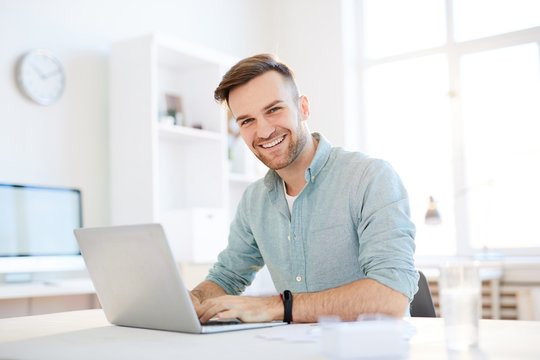 Portrait of handsome young man smiling at camera while using laptop in office, copy space