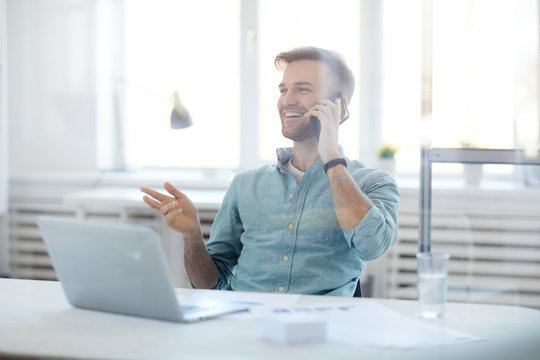 Portrait of handsome young man laughing cheerfully while speaking by phone sitting at desk in office, copy space
