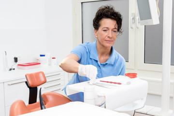 Zahnarzthelferin bereitet die Instrumente für eine Behandlung vor