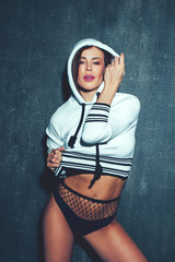 Sensual hip-hop dancer holding hoodie at night