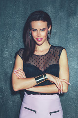 Fashionable stylish brunette woman posing at wall in night