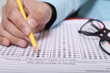 Man is filling OMR sheet with pencil. Picture of glasses on the OMR sheet.