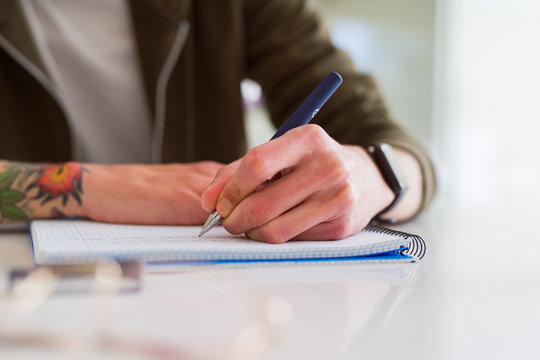 Close up of man hands writing on notebook, working taking notes