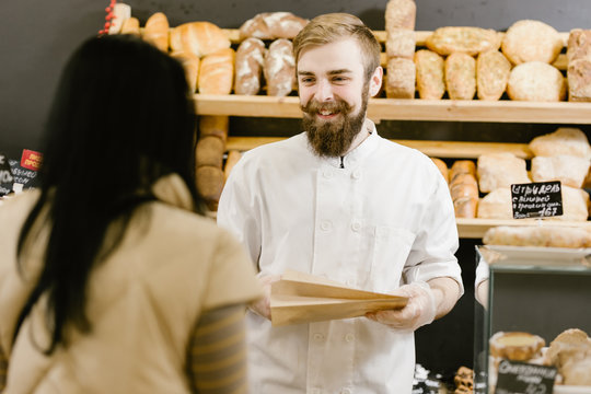Charismatic baker with a beard and mustache gives a paper bag of bread to the customer in the bakery