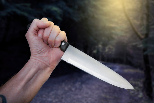 Horror scene of murderer or maniac's hand with large butcher knife in creepy woods scanario Halloween themed scene.